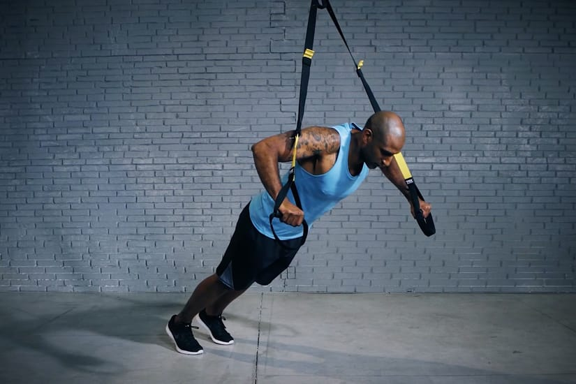 Man doing chest press with TRX