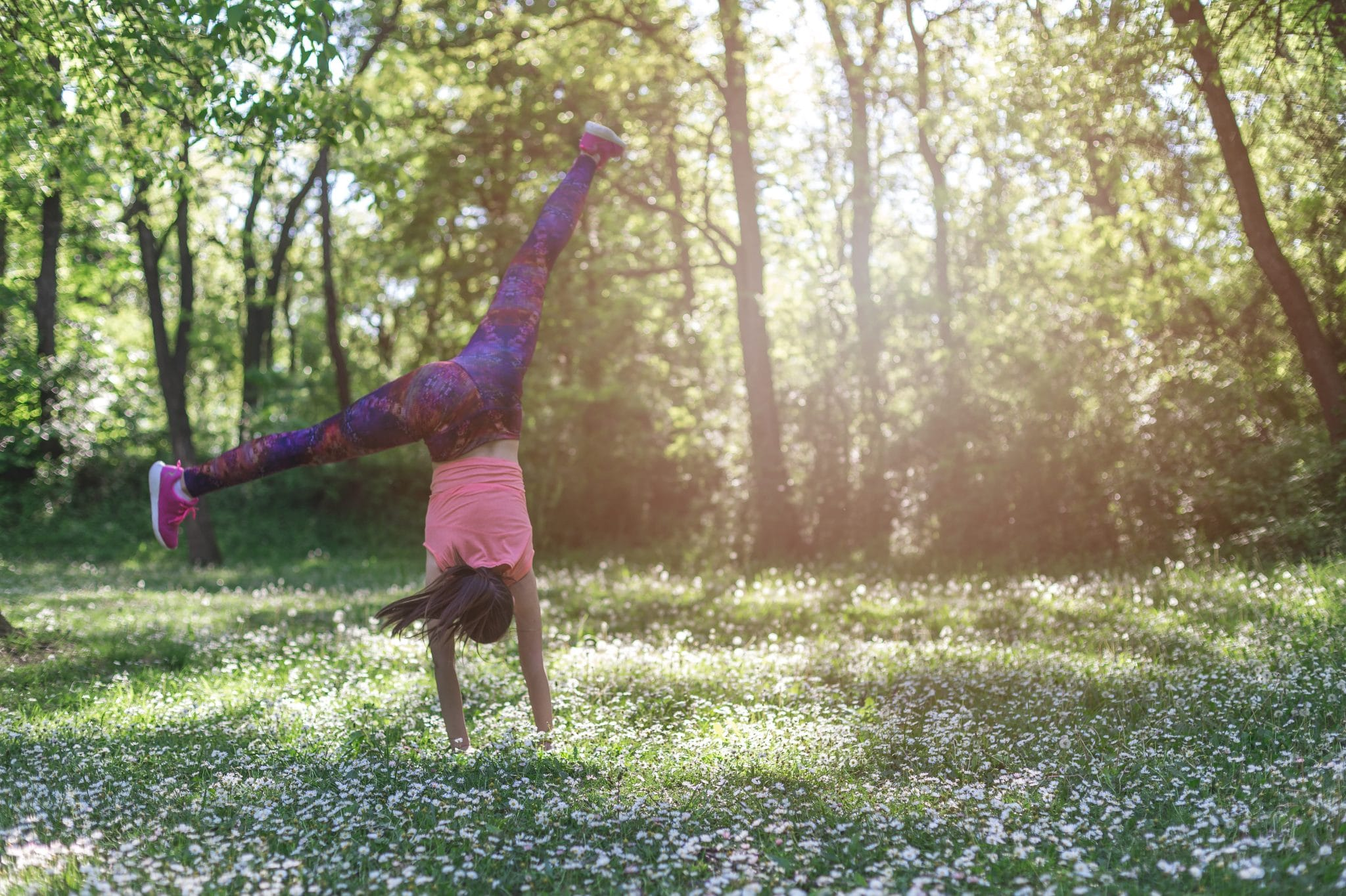 sport girl makes a cartwheeling on a field of flowers - sunny day in a park/forest